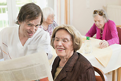 Caretaker reading newspaper with senior woman in rest home, Bavaria, Germany