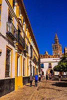 People walking from the Alcazar Palace toward the Giralda Tower and Seville Cathedral, Seville, Andalusia, Spain.