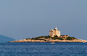 A lighthouse light house on an island outside the village, blue mountains in the background. Dinghy. Grainy. Orebic town, holiday resort on the south coast of the Peljesac peninsula. Orebic town. Peljesac peninsula. Dalmatian Coast, Croatia, Europe.