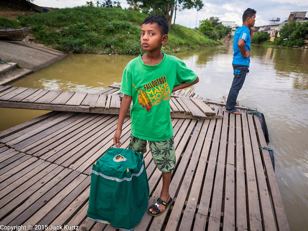 16 JUNE 2015 - SUNGAI KOLOK, THAILAND:  A boy waits to get on a small boat in Sungai Kolok to cross into Malaysia. The border between Thailand and Malaysia in Sungai Kolok, Narathiwat, Thailand. Thai and Malaysians cross the border freely for shopping and family visits. The border here is the Kolok River (Sungai is the Malay word for river).        PHOTO BY JACK KURTZ