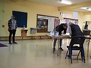 Early morning voters are checked in at this Pennsylvania polling station. One election clerk reads the name aloud and a second one records that this person is voting in person.