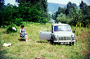 Woman reading by Austin Mini van camping in countryside area, Romania, eastern Europe 1967