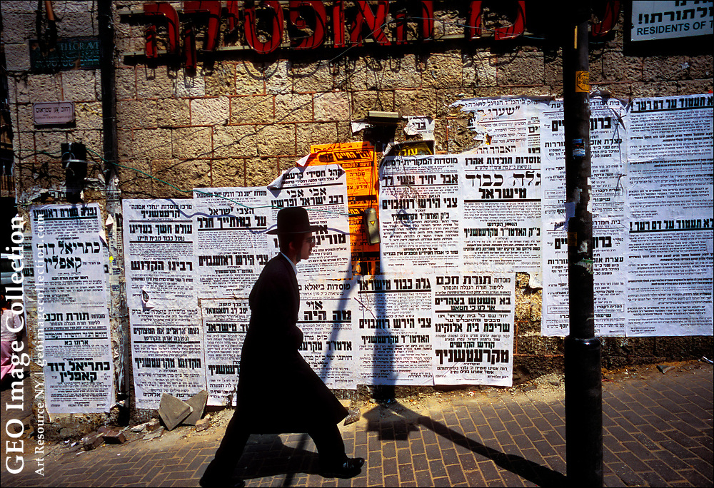 """An Orthodox Jew in traditional 18th Century """"kapotas"""" and """"shtreimel,"""" or coat and hat, walks past death notices posted in the Me'a She'arim Quarter of Jerusalem, the most famous Jewish Orthodox community in the world.  It is also one of Jerusalem's poorest neighborhoods with families of as many 10 people crowded into two-room apartments."""