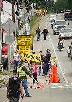 Vendors try to drum up business in Weirs Beach on Tuesday with a slower traffic pace during the mid week dampness.  (Karen Bobotas/for the Laconia Daily Sun)