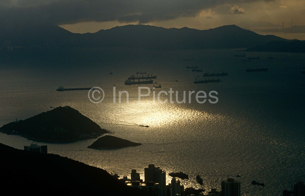 Seen from a hilltop, an aerial landscape of Lantau Island and cargo shipping at anchor in West Lamma Channel in the Hong Kong Territories. With a pool of sunlight from otherwise heavy clouds, the waters of the Channel are calm as we look towards the southern shores of Hong Kong Island. Lamma Island is the third largest island in Hong Kong, administratively part of the Islands District. It lies southwest to the of Hong Kong, China with has an area of 13.55km. The Channel is an anchoring point for large cargo vessels awaiting crews or offloading.