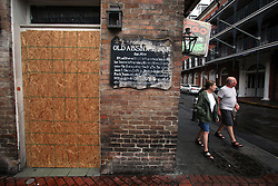 28 August 2012. New Orleans, Louisiana,  USA. <br /> Tourists pass by the boarded up Absinthe House on Bourbon Street in the French Quarter ahead of Hurricane Isaac. The 7th year anniversary of Hurricane Katrina is tomorrow and with a storm lurking in the Gulf many have evacuated as an uneasy calm settles over New Orleans.<br /> Photo; Charlie Varley