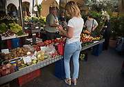 Greve in Chianti, Tuscany, Italy. June 2018<br /> Market in the Piazza<br /> Greve in Chianti (the old name was Greve; in 1972 it was renamed Greve in Chianti after the inclusion of that area in the Chianti wine district) is a town and comune (municipality) in the Metropolitan City of Florence, Tuscany, Italy. It is located about 31 kilometres (19 mi) south of Florence and 42 kilometres (26 mi) north of Siena.<br /> The piazza is fronted by numerous medieval aged buildings, including the 11th century Chiesa Santa Croce which was rebuilt in 1325 after being burned to the ground, along with the rest of the town, by the Duke of Lucca, Castruccio Castracani. After further renovation, the church, which houses paintings of the school of Fra Angelico, now features a neo-classical façade. In the piazza there is also a monument to navigator Giovanni da Verrazzano, who was possibly born nearby