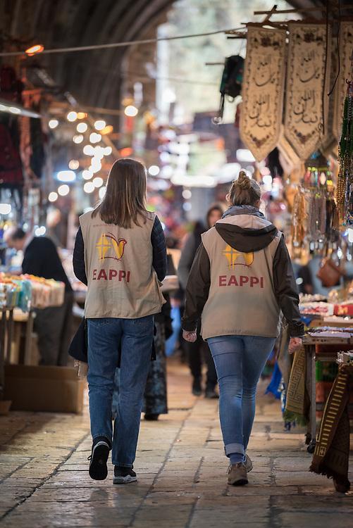 29 February 2020, Jerusalem: Ecumenical Accompaniers Kristin (left) and Charlotte (right) walk through a market street in the Muslim Quarter of the Jerusalem Old City.