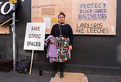 © Licensed to London News Pictures; 09/10/2021; Bristol, UK. SOPHIA KHAN stands outside the Hidden Corner cafe and bookshop in St Pauls that she and her partner Aaron Onuora have been locked out of by the landlord, Presman, during a protest against gentrification and the closure of a black owned business and LGBTQI+ friendly space. The couple run Hidden Corner which stocks books including fiction, non-fiction and children's books, mostly by people of colour (POC) and queer authors, and has a cafe with affordable prices for the local St Pauls community and other disadvantaged groups. On 04 October Sophia went to open the cafe only to find the door locked with chains and a notice from the landlord saying they re-entered the property under a clause in the lease. Sophia says they have always paid the rent on time. Sophia has said they have had some recent difficulties with the landlord and were made to feel their business did not fit with the image the owner wanted to present to Airbnb guests who come to stay on the floors above. Photo credit: Simon Chapman/LNP.