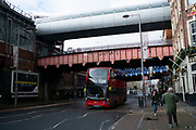 Double decker bus passes underneath old and new bridges outside Waterloo railway station in London, United Kingdom.