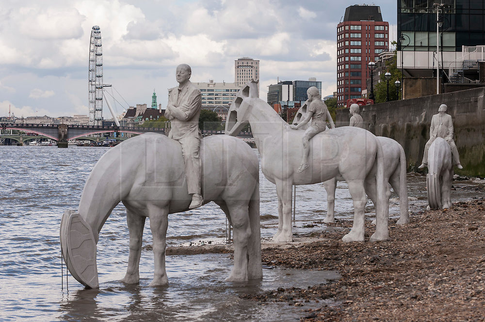"""© Licensed to London News Pictures. 02/09/2015 London, UK. The art installation entitled """"The Rising Tide"""" (comprising four horse-riders on horses with petroleum pumps for heads) by the underwater eco-sculptor Jason deCaires Taylor, stands on the foreshore of the River Thames in Vauxhall and is revealed with each low tide.  The installation aims to question man's reliance on fossil fuels and is part of this year's Totally Thames festival. Photo credit : Stephen Chung/LNP"""