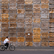 A young boy biccyles past a group of stacked fruit crates in downtown Yakima Washington.
