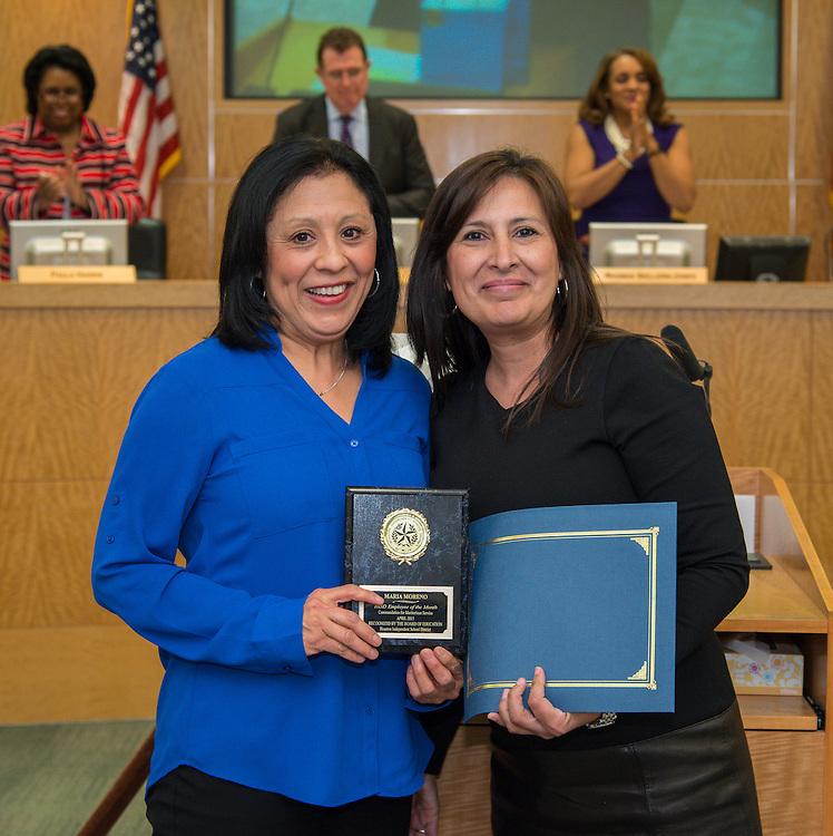 Maria Moreno, left, accepts the Employee of the Month award from Margarita Gardea, right, during the Houston ISD board of trustees meeting, March 12, 2015.