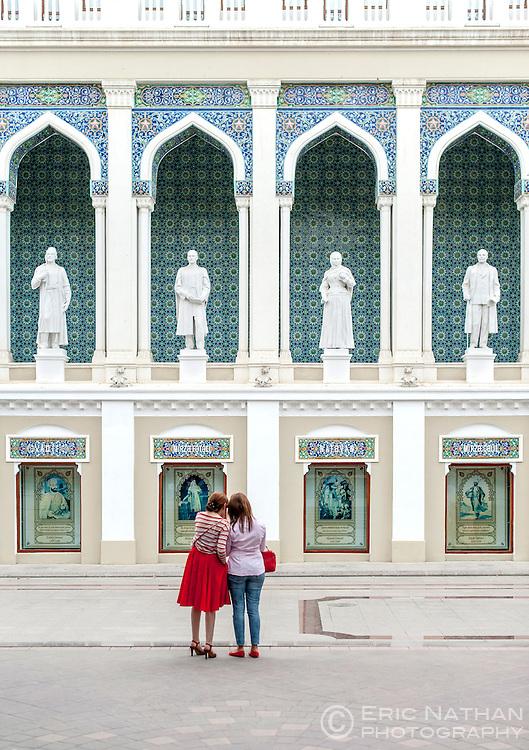 Two women standing in front of the Nizami Museum of Azerbaijan Literature in Baku.