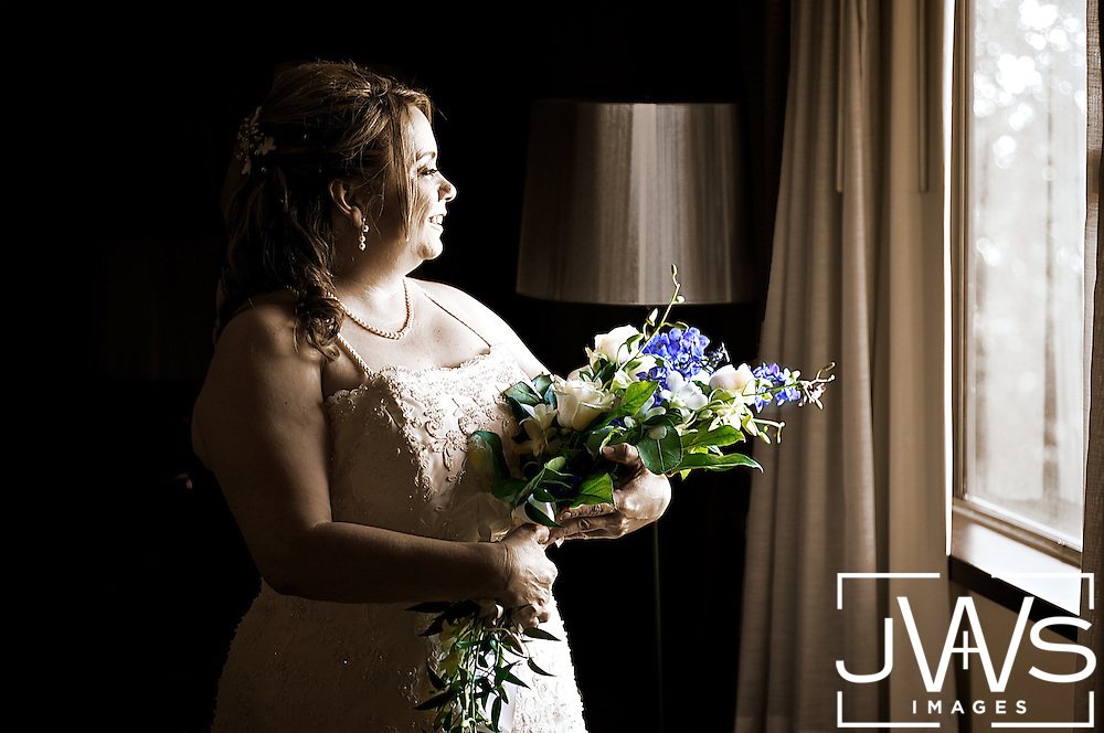Black and white picture with colorful flowers being held by bride in her hotel room before her wedding.