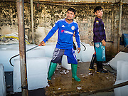 """11 JUNE 2015 - MAHACHAI, SAMUT SAKHON, THAILAND:  Burmese migrant workers in Mahachai sell ice blocks to shrimp packers. Labor activists say there are about 200,000 migrant workers from Myanmar (Burma) employed in the fishing and seafood industry in Mahachai, a fishing port about an hour southwest of Bangkok. Since 2014, Thailand has been a Tier 3 country on the US Department of State Trafficking in Persons Report (TIPS). Tier 3 is the worst ranking, being a Tier 3 country on the list can lead to sanctions. Tier 3 countries are """"Countries whose governments do not fully comply with the minimum standards and are not making significant efforts to do so."""" After being placed on the Tier 3 list, the Thai government cracked down on human trafficking and has taken steps to improve its ranking on the list. The 2015 TIPS report should be released in about two weeks. Thailand is hoping that its efforts will get it removed from Tier 3 status and promoted to Tier 2 status.       PHOTO BY JACK KURTZ"""