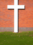 Large white crucifix cross against brick wall on grass lawn River of Life Church, Felixstowe, Suffolk, England