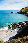 Hidden pebbly bay surrounded by rocks and cliffs on the North Coast of Jersey, CI