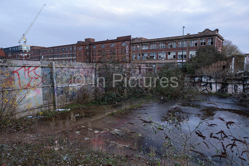View looking across overgrown and disused waste ground, awaiting redevelopment, which seems to have stalled in the last year in the industrial area of Deritend, which lies less than half a mile from the city centre on 14th December 2020 in Birmingham, United Kingdom. Birmingham is undergoing a massive transformation called the Big City Plan which involves the controversial regeneration of the city centre as well as a secondary zone reaching out further. The Big City Plan is the most ambitious, far-reaching development project being undertaken in the UK. The aim for Birmingham City Council is to create a world-class city centre by planning for the next 20 years of transformation.