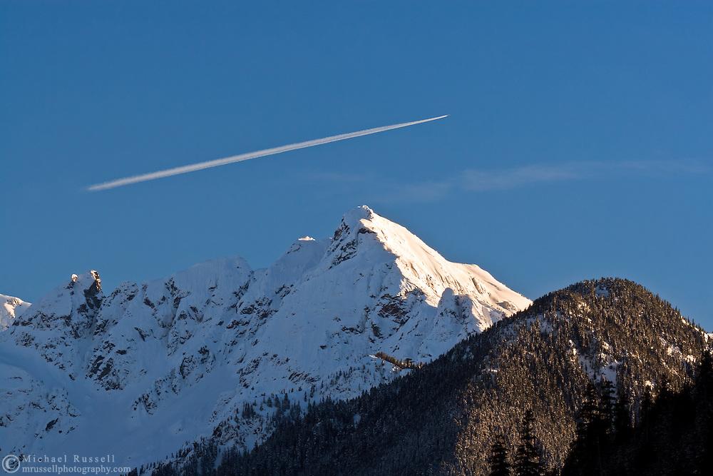 An airplane flies over Nodoubt Peak in North Cascades National Park, Washington State, USA.