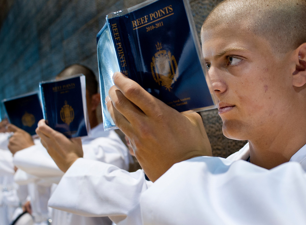 """A incoming midshipman reads his Reef Points book during while wating for further instructions on his first day at the U.S. Naval Academy in Annapolis, MD. Approximately 1,230 young men and women arrived at the U.S. Naval Academy's Alumni Hall, Thursday, July 1, for Induction Day to begin their new lives as """"plebes"""" or midshipmen fourth class (freshmen). """"I-Day"""" culminates when the members of the Class of 2014 take the oath of office at a ceremony at 6 p.m. in Tecumseh Court, the historic courtyard of the Bancroft Hall dormitory. Over 17,400 young men and women applied to be members of the Naval Academy Class of 2014 - a record for USNA."""