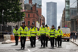 © Licensed to London News Pictures. 30/08/2019. Manchester, UK. Police on Deansgate as Extinction Rebellion block roads in Manchester City Centre , at the start of several days of planned disruption organised by environmental campaigners . Manchester City Council has declared a climate emergency but activists say the council's development plans do not reflect this . Photo credit: Joel Goodman/LNP