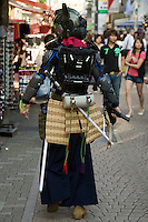 """Takeshita Street Samurai - A wide variety of """"costume play"""" getups are shown here: goths, cartoon characters from Japanese manga, anime,  the sweet-and-innocent frilly look or combinations in between (goth lolly)  Every Sunday, these cosplay characters converge on Harajuku, Tokyo's fashion quarter. Most casual observers say that cosplay is a reaction to the rigid rules of Japanese society. But since so many cosplay girls congregate in Harajuku and Aoyama - Tokyo headquarters of Fendi, Hanae Mori and Issey Miyake, others consider it is a reaction to high fashion. Whatever the cause, cosplay aficionados put a tremendous amount of effort into their costumes every Sunday. One wonders what they wear on Monday morning..."""