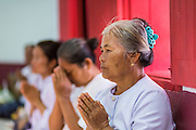 29 JUNE 2014 - DAN SAI, LOEI, THAILAND: Women pray during a ceremony in Wat Ponchai on the last morning of the Ghost Festival. Phi Ta Khon (also spelled Pee Ta Khon) is the Ghost Festival. Over three days, the town's residents invite protection from Phra U-pakut, the spirit that lives in the Mun River, which runs through Dan Sai. People in the town and surrounding villages wear costumes made of patchwork and ornate masks and are thought be ghosts who were awoken from the dead when Vessantra Jataka (one of the Buddhas) came out of the forest. On the last day of the festival people participate in merit making ceremonies at the Wat Ponchai in Dan Sai and lead processions through town soliciting donations for the temple.    PHOTO BY JACK KURTZ