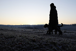 © Licensed to London News Pictures. 12/12/2017. Epsom, UK. A man walks his dog on Epsom Downs after a night of freezing sub zero temperatures. Photo credit: Peter Macdiarmid/LNP