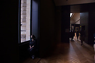 A woman watching the landscape while taking rest at Louvre Museum