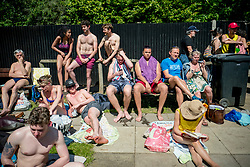 © Licensed to London News Pictures. 06/05/2018. London, UK. People sunbathe near Hampstead Heath Mixed Bathing Pond in north London as temperatures hit 27C on Sunday, May 6, 2018. Photo credit: Tolga Akmen/LNP
