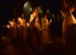 © Licensed to London News Pictures. 11/12/2015. York, UK. The Chorus Pictor choir from Stockholm and the YASS Lucia Singers process during the Sankta Lucia Carol Service at York Minster. Lucia is a tradition in the Swedish calendar and is a celebration of St Lucy as the bringer of  light in the darkness of winter.  Photo credit : Anna Gowthorpe/LNP