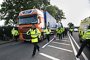 12 local activists locked themselves in specially made arm tubes to block the entrance to Quadrillas drill site in New Preston Road, July 03 2017, Lancashire, United Kingdom. Police escorting a Quadrilla delivery to the site. The 13 activists included 3 councillors; Julie Brickles, Miranda Cox and Gina Dowding and Nick Danby, Martin Porter, Jeanette Porter,  Michelle Martin, Louise Robinson,<br /> Alana McCullough, Nick Sheldrick, Cath Robinson, Barbara Cookson, Dan Huxley-Blyth. The blockade is a repsonse to the emmidiate drilling for shale gas, fracking, by the fracking company Quadrilla. Lancashire voted against permitting fracking but was over ruled by the conservative central Government. All the activists have been active in the struggle against fracking for years but this is their first direct action of peacefull protesting. Fracking is a highly contested way of extracting gas, it is risky to extract and damaging to the environment and is banned in parts of Europe . Lancashire has in the past experienced earth quakes blamed on fracking.