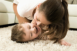 Mother and son are romping in living room, smiling