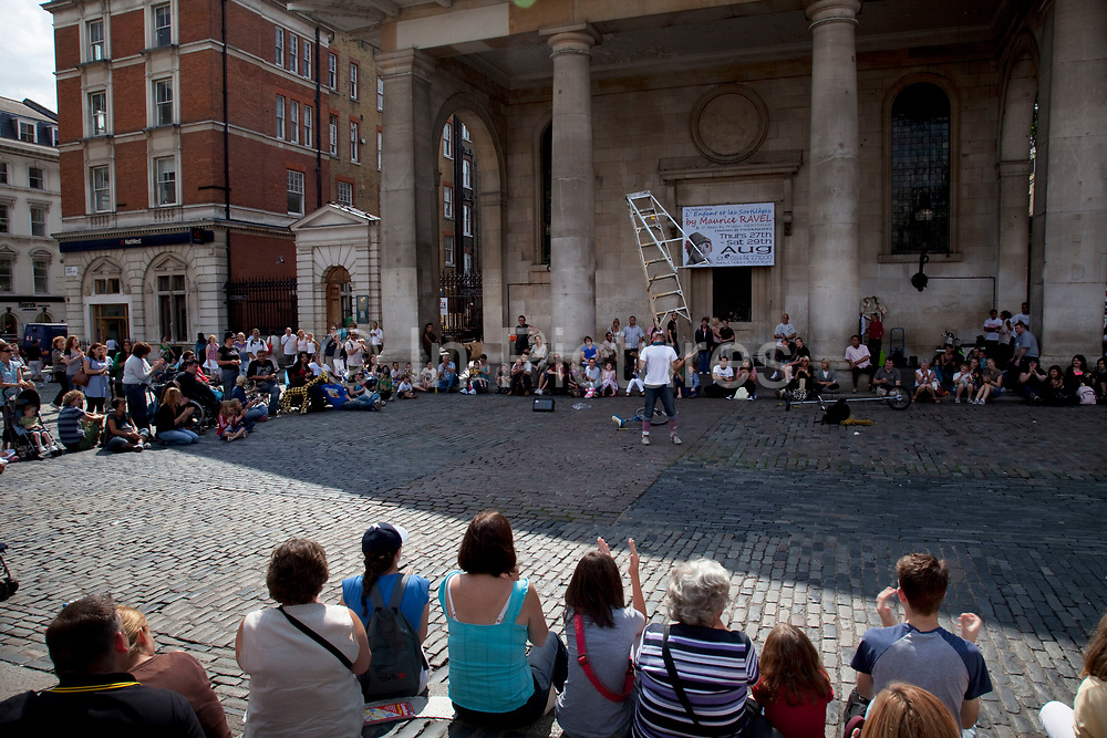 Busking street performer plays for an audience of onlookers at Covent Garden, Central London. The performance is somewhat acrobatic, involving the gathered tourists.