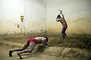 An Indian Khusti wrestler prepares the mud training area at a wrestling Akhara while his friend limbers up in New Delhi, India. <br /> Pehlwani, or kusti is a form of wrestling from South Asia. It was developed in the Mughal Empire<br /> by combining native malla-yuddha with influences from Persian koshti pahlavani. A practitioner of this sport is referred to as a pehlwan.