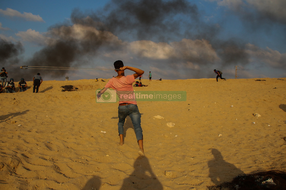October 8, 2018 - Dozens of Palestinian demonstrators are injured by Israeli live ammunition and tear gas during clashes with Israeli military forces along the northern Gaza Strip near the beach of Zakim. Some Palestinian protesters burned tyres and threw rocks towards the Israeli troops on the other side of the fence, and according to the Israeli army some explosive devices were also hurled in the direction of the fence. Protesters were calling for the lift of the air, land and water blockade imposed by Israel on the Palestinian enclave since 2007 when Hamas took power in Gaza after winning the elections. Israel maintains that the blockade, which has also been enforced by Egypt, is a necessary measure to prevent Hamas and other militant groups in Gaza to arm or build military infrastructure. Yet, the World Bank has openly stated that Gaza's economy is on the brink of collapse with the blockade playing a big part in that (Credit Image: © Ahmad Hasaballah/IMAGESLIVE via ZUMA Wire)