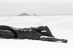 man in a bikini resting on sand in the desert