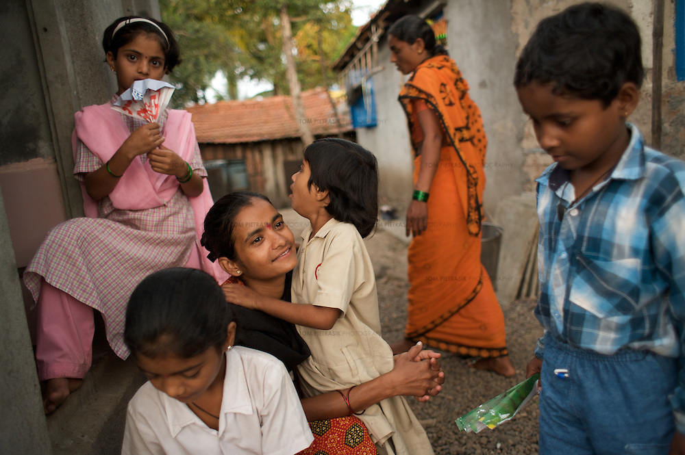 """At home Vasanti (centre) and daughters Shrudha, 10 (HIV positive, in pink), Shubhada, 11 (HIV negative, foreground) and Vrinda, 8 (status not known). Vasanti Shinde, 26, works for the Save Foundation. <br /> <br /> Like many of the women who work for and with UNDP partners the Save Foundation, Vasanti Shinde, age 26, only found out that she was HIV positive after her husband became seriously ill with an AIDS-related illness five years ago. Vasanti's husband subsequently died. Vasanti now lives with her two younger daughters Shrudha, age 10, and Vrinda, 8, in the one-room home of her brother in Sangli city. Vasanti's elder daughter, eleven year old Shubhada is being brought up by her paternal grandmother and sees her mother during holidays. Vasanti knows that Shubhada is HIV negative and Shruda is positive but anxiety over the result means that she refuses to have Vrinda tested for HIV. For a monthly income of Rs.3500, Vasanti works as a field officer and counselor for the Save Foundation. She works in the positive-people's pharmacy for no pay. Her work with the Save Foundation entitles her access to a credit union which provides low interest loans covering medical expenses. Though first-line drugs and homeopathic medicine keep Vasanti healthy, she is prone to infection and recently suffered a bout of influenza. Vasanti is completely open about her HIV status and most of her neighbours know that she is HIV positive. Vasanti says that """"I used to feel like I was going to die. Now, because of the Save Foundation, I feel like I'm going to live."""" <br /> <br /> Photo: Tom Pietrasik<br /> Sangli, Maharashtra. India<br /> August 28th 2008"""