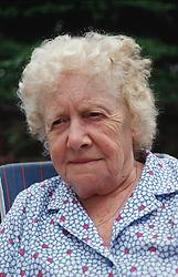 Portrait of elderly woman sitting outside,