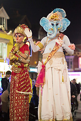 """© Licensed to London News Pictures. 01/11/2015. Leicester, UK. More than 35,000 people were estimated to have attended the annual Diwali light switch-on which took place along the named """"Golden Mile"""" in Belgrave Road, Leicester. Pictured, Figures on stilts make their way along the Belgrave Road ready for the lights switch-on. Photo credit : Dave Warren/LNP"""