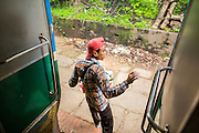 15 JUNE 2013 - YANGON, MYANMAR:  A vendor hops off the Yangon Circular Train at a stop. Yangon Circular Railway is the local commuter rail network that serves the Yangon metropolitan area. Operated by Myanmar Railways, the 45.9-kilometre (28.5mi) 39-station loop system connects satellite towns and suburban areas to the city. The railway has about 200 coaches, runs 20 times and sells 100,000 to 150,000 tickets daily. The loop, which takes about three hours to complete, is a popular for tourists to see a cross section of life in Yangon. The trains from 3:45 am to 10:15 pm daily. The cost of a ticket for a distance of 15 miles is ten kyats (~nine US cents), and that for over 15 miles is twenty kyats (~18 US cents). Foreigners pay 1 USD (Kyat not accepted), regardless of the length of the journey.     PHOTO BY JACK KURTZ