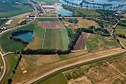 Nederland, Gelderland, Heerewaarden 08-07-2010; Heerewaardense afsluitdijk (voorgrond) en Maasdijk, links met wiel, restant van een vroeger dijkdoorbraak. Op deze plek, in de Gemeente Heerwaarden, naderen de twee rivieren Waal en Maas elkaar het meest. In het verleden liepen de twee rivieren bij hoog water in elkaar over (met alle problemen van dien)..Heerewaardense dam (foreground) and Maasdijk (left). On this spot the two rivers Waal and Maas approach each other the most. In the past the rivers would 'connect' with high water, causing serious water management problems..luchtfoto (toeslag), aerial photo (additional fee required).foto/photo Siebe Swart