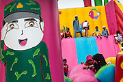 "07 JULY 2013 - NARATHIWAT, NARATHIWAT, THAILAND:   Thai Muslim children play in a ""bouncy house"" set up by Royal Thai Marines Sunday. Royal Thai Marines in Narathiwat province held a special ceremony Sunday in advance of Ramadan. They presented widows, orphans and indigent people with extra rice and food as a part of the Thai government's outreach to resolve the Muslim insurgency that has wracked southern Thailand since 2004. The Holy Month of Ramadan starts on about July 9 this year. Muslims are expected to fast from dawn to dusk, engage in extra prayers, recitation of the Quran and perform extra acts of charity during Ramadan. It is the holiest month of the year for Muslims.  PHOTO BY JACK KURTZ"