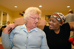 A Care Assistant chats to an elderly lady in her chair in a multi-cultural day centre; Bradford,