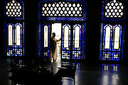 Man on a balcony inside an old palace in Fez medina. Many of these old palaces, also called ryads, have been converted to small luxury hotels.