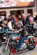 A biker wearing cow horns on his helmet rides down Main Street during the 74th Annual Daytona Bike Week March 8, 2015 in Daytona Beach, Florida. More than 500,000 bikers and spectators gather for the week long event, the largest motorcycle rally in America.