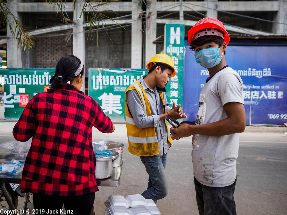 "12 FEBRUARY 2019 - SIHANOUKVILLE, CAMBODIA:  A Cambodian woman (left) sells street food to a Chinese construction worker (center) and a Cambodian construction worker in front of the Blue Bay, a Chinese casino and resort development in Sihanoukville. There are about 50 Chinese casinos and resort hotels either open or under construction in Sihanoukville. The casinos are changing the city, once a sleepy port on Southeast Asia's ""backpacker trail"" into a booming city. The change is coming with a cost though. Many Cambodian residents of Sihanoukville  have lost their homes to make way for the casinos and the jobs are going to Chinese workers, brought in to build casinos and work in the casinos.      PHOTO BY JACK KURTZ"