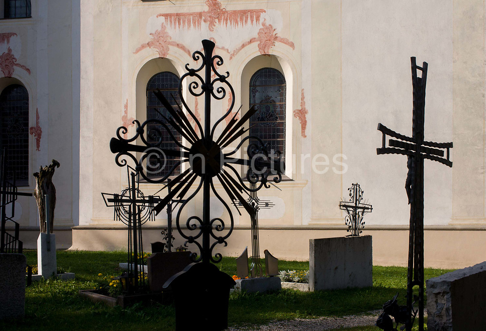 Typical Dolomites church architecture and graveyard ironwork in Leonhard-St Leonardo, a Dolomites village in the Badia region of south Tyrol, Italy. The church of San Leonardo and its Gothic tower was built between 1776 and 1778 by Franz Singer on a previous medieval building consecrated in 1347. South Tyrol is a very religious and traditional country. The weekly walk to Mass and the celebration of religious festivals and processions are part of the culture and tradition in South Tyrol. In almost every house you will find a cross on a corner with consecrated palm branches over there. Also in the stable there are consecrated palm branches to keep away every disaster. South Tyroleans are almost all Catholics and quite conservative. San Leonardo is in the municipality of Badia populated mostly by people who speak the ancient Ladin language.