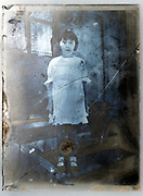 severely deteriorating glass plate with young girl standing France ca 1920s
